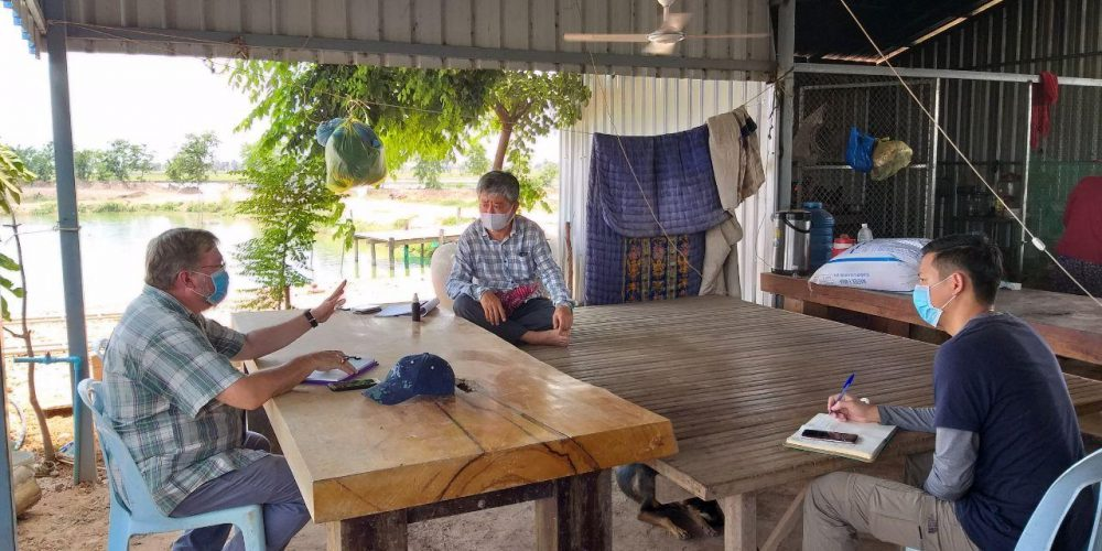 From Left: CAST Technical Advisor Len Rogers follows social distancing and hygiene practices as he shares recommendations on feeding practices and discusses current market conditions with fish farm owner Mr. Sok Raden and CAST Technical Specialist David Samveana at  Mr. Raden's farm.
